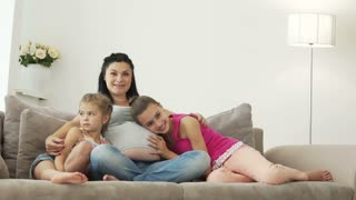 Pregnant woman sitting on a couch with her daughters and they laughing