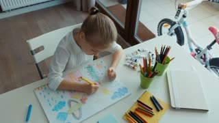 Preschooler girl laughing. Portrait child painting a picture. Looking at camera. Thumbs up. Ok. Top view. Zooming