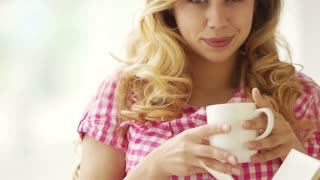 Pretty blond girl holding cup of drink and smiling at camera