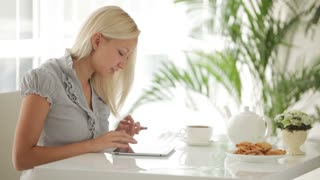 Pretty blonde girl sitting at kitchen table with touchpad and smiling at camera