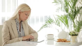 Pretty businesswoman sitting at table using touchpad and smiling at camera
