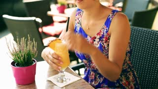 Pretty girl drinking cocktail with pineapple and smiling to the camera