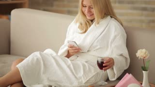 Pretty girl in bathrobe sitting on sofa using cellphone drinking wine looking at camera and smiling. Panning camera