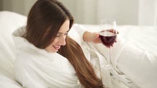 Pretty girl lying in bed holding glass of wine using laptop and smiling. Panning camera