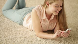 Pretty girl lying on floor using mobile phone looking at camera and smiling. Panning camera