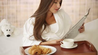 Pretty girl relaxing in bed reading newspaper looking at camera and smiling. Panning camera