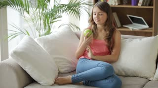 Pretty girl relaxing on couch eating apple looking at camera and smiling