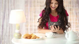Pretty girl sitting at cafe using mobile phone and smiling at camera