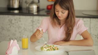 Pretty girl sitting at kitchen table eating salad looking at camera and smiling