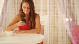 Pretty girl sitting at table at cafe using mobile phone and smiling at camera. Panning camera