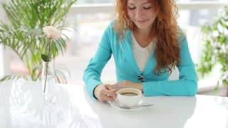 Pretty girl sitting at table drinking coffee and smiling