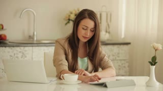 Pretty girl sitting at table using touchpad and laptop drinking tea and smiling at camera