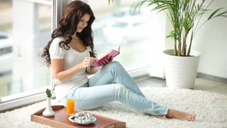Pretty girl sitting by window reading book closing it and smiling at camera