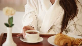 Pretty girl sitting in bed drinking tea looking at camera and smiling. Panning camera