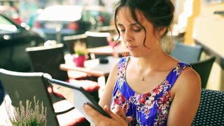 Pretty girl sitting in the street restaurant and surfing on tablet