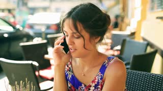 Pretty girl sitting in the street restaurant and talking on cellphone