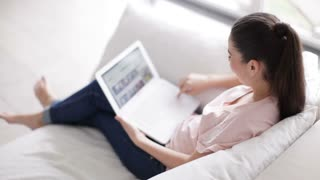 Pretty girl sitting on couch with laptop and looking at camera with smile