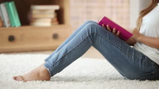Pretty girl sitting on floor reading book closing it looking at camera and smiling. Panning camera