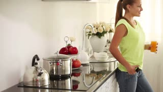 Pretty girl standing in kitchen holding glass of juice and smiling at camera. Panning camera