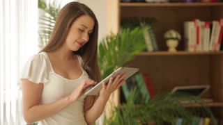 Pretty girl standing with touchpad looking at camera and smiling