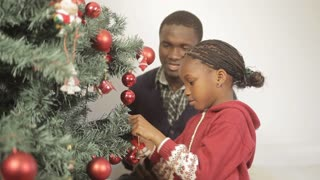 Pretty girl with her father decorating the christmas tree