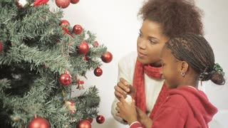 Pretty girl with her mom decorating the christmas tree