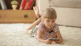 Pretty little girl lying on floor with mobile phone looking at camera and smiling