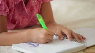 Pretty little girl lying on sofa drawing in notebook and smiling at camera