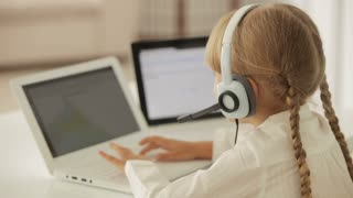 Pretty little girl sitting at desk with headset using laptop looking at camera and smiling