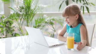Pretty little girl sitting at table drinking juice using laptop and smiling