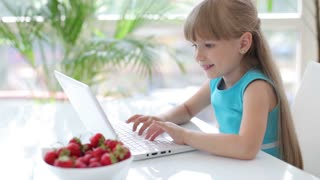 Pretty little girl sitting at table eating strawberries using laptop and smiling at camera