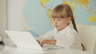 Pretty little girl sitting at table studying with her laptop and smiling at camera