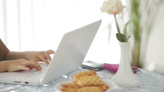 Pretty little girl sitting at table using laptop and smiling happily at camera