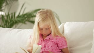 Pretty little girl sitting on sofa with book and smiling