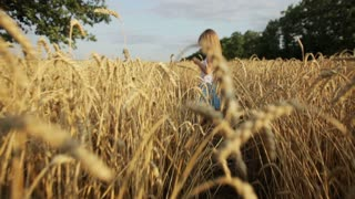 Pretty little girl standing in the middle of wheat field and smiling at camera