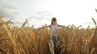 Pretty little girl walking through wheat field stretching out her arms and smiling