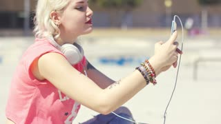 Pretty trendy young blond woman taking a selfie outdoors in the summer sunshine on her mobile phone close up profile view