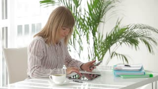 Pretty woman sitting at table using touchpad talking on mobile phone and smiling at camera