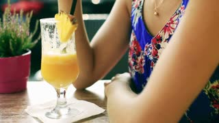 Pretty woman sitting in the street cafe and drinking pineapple drink
