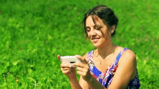 Pretty woman sitting on green meadow and texting on smartphone