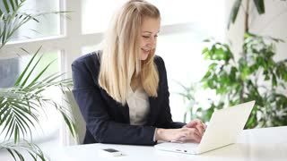 Pretty young business woman sitting at office table using laptop closing it and looking at camera smiling