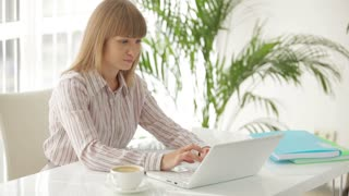 Pretty young businesswoman sitting at table working on laptop and writing in notebook