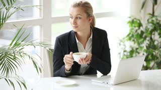 Pretty young woman at office sitting at table holding cup of coffee using laptop and smiling at camera