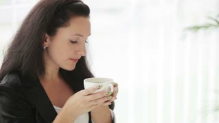 Pretty young woman drinking coffee looking at camera and smiling
