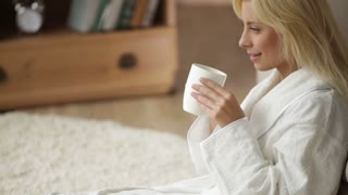 Pretty young woman in bathrobe sitting on floor drinking from cup looking at camera and smiling. Panning camera