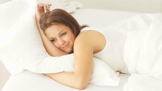 Pretty young woman lying in bed and smiling at camera