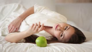 Pretty young woman lying on bed playing with green apple looking at camera and smiling. Panning camera