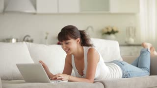 Pretty young woman lying on couch using laptop and smiling