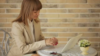 Pretty young woman sitting at cafe and using laptop