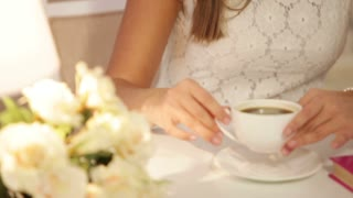 Pretty young woman sitting at cafe drinking tea looking at camera and smiling. Panning camera